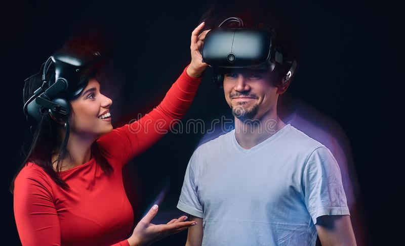 Young joyful girl adjusts virtual reality glasses on her boyfriend. Couple gamers with VR headsets. Isolated on dark background. Photo with light effect royalty free stock photo
