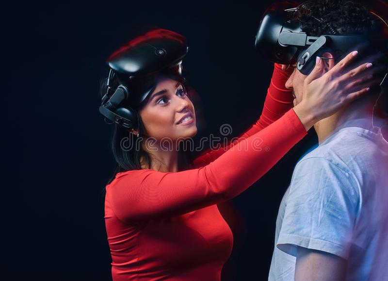 Young joyful girl adjusts virtual reality glasses on her boyfriend. Couple gamers with VR headsets. Isolated on dark background. Photo with light effect stock image