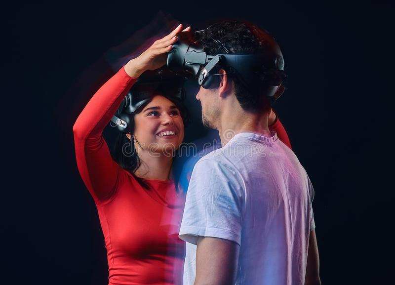 Young joyful girl adjusts virtual reality glasses on her boyfriend. Couple gamers with VR headsets. Isolated on dark background. Photo with light effect royalty free stock image