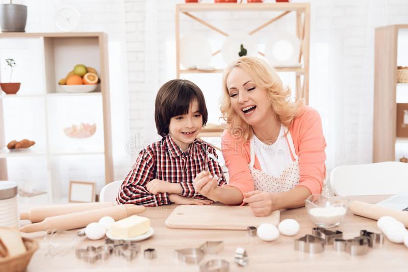 Young joyful grandmother, holding baking dish in her hand, and grandson in plaid shirt are sitting in kitchen. stock photos