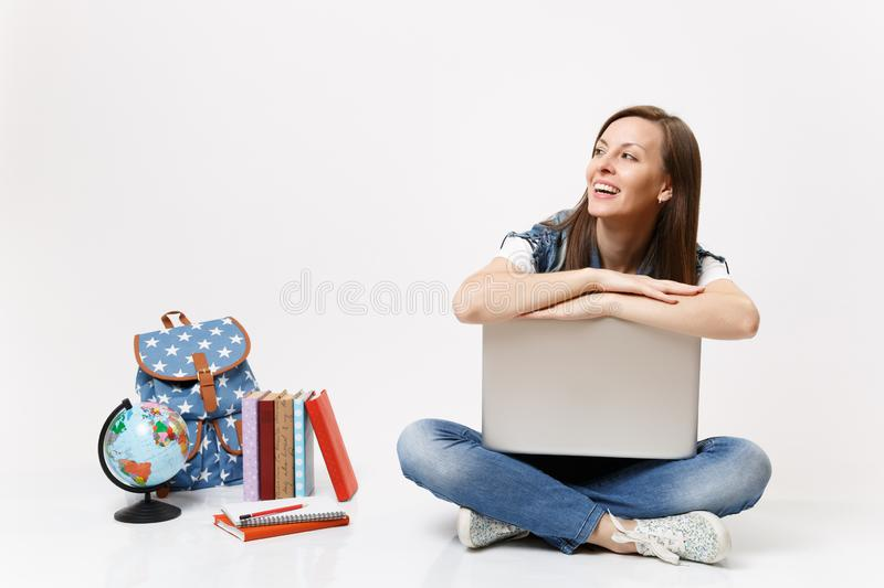 Young joyful laughing woman student leaning on laptop pc computer looking aside sitting near globe, backpack, school stock image