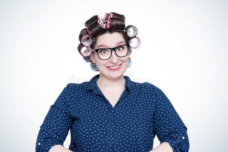 Young joyful positive smiling girl in glasses and hair curlers on her head. royalty free stock photos