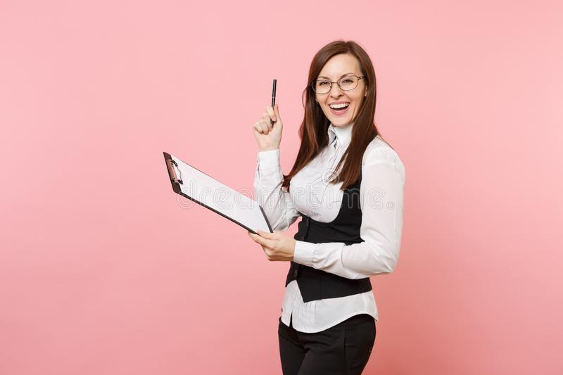 Young joyful successful business woman in glasses holding clipboard tablet with papers document and pen on pink stock photo