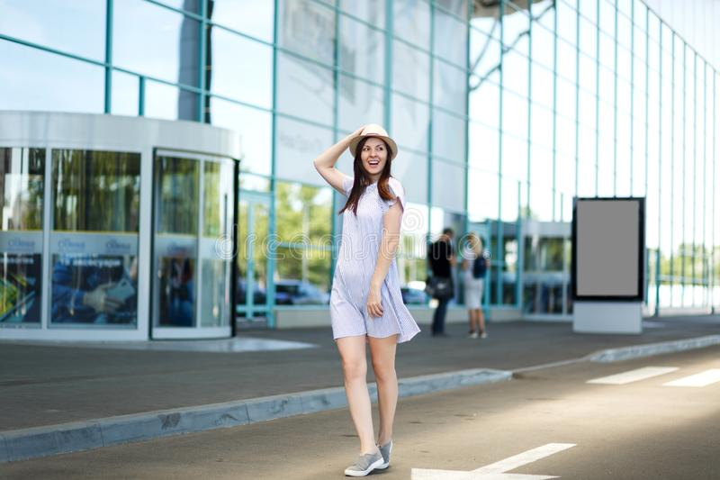 Young joyful traveler tourist woman in hat and light clothes standing at international airport. Female passenger. Traveling abroad to travel on weekends getaway royalty free stock photo