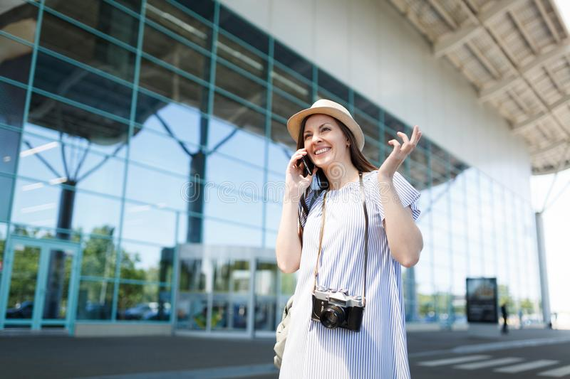 Young joyful traveler tourist woman with retro vintage photo camera talk on mobile phone call friend booking taxi, hotel royalty free stock photography