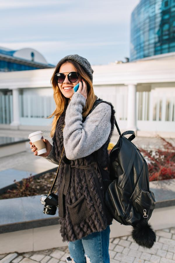 Young joyful woman with coffee to go walking on sunny cold day in big city. Pretty girl wearing warm winter wollen stock photos