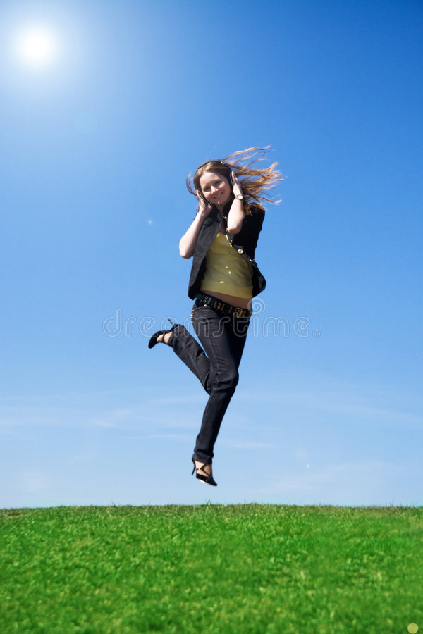 Download The Young Jumping Girl With Headphones Stock Image - Image: 4863607