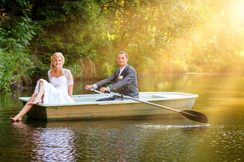 Young just married bride and groom on boat stock photography