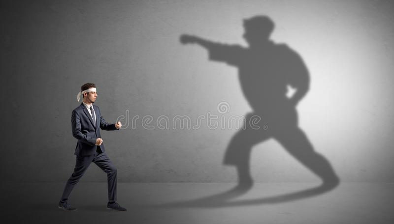 Karate man confronting with his own shadow. Young karate man confronting with his own shadow stock photography