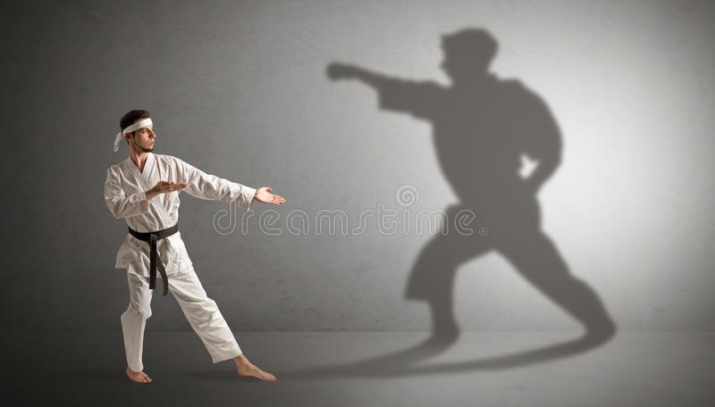 Karate man confronting with his own shadow. Young karate man confronting with his own shadow royalty free stock photography