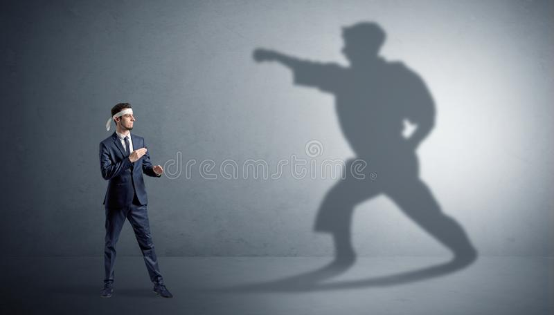 Karate man confronting with his own shadow. Young karate man confronting with his own shadow stock photos