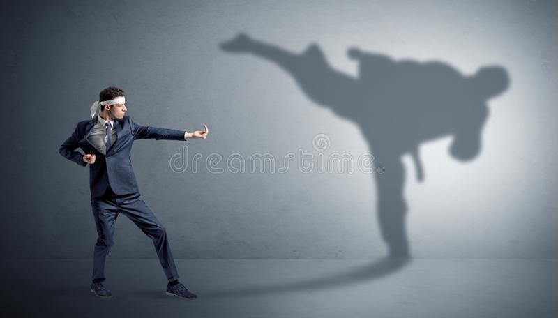 Karate man confronting with his own shadow. Young karate man confronting with his own shadow royalty free stock photo