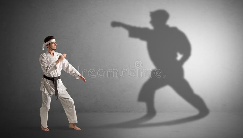 Karate man confronting with his own shadow. Young karate man confronting with his own shadow royalty free stock image
