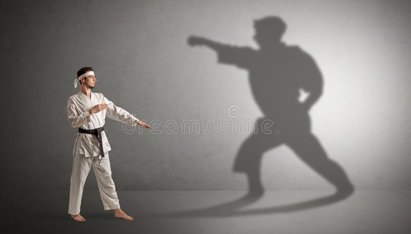 Karate man confronting with his own shadow. Young karate man confronting with his own shadown royalty free stock images