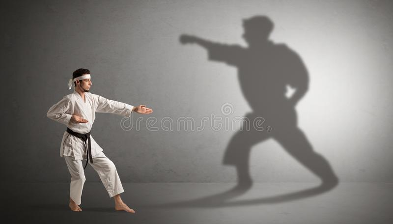 Karate man confronting with his own shadow. Young karate man confronting with his own shadown stock photo