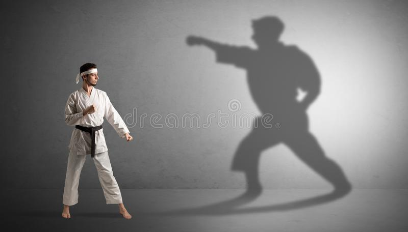 Karate man confronting with his own shadow. Young karate man confronting with his own shadown stock photos