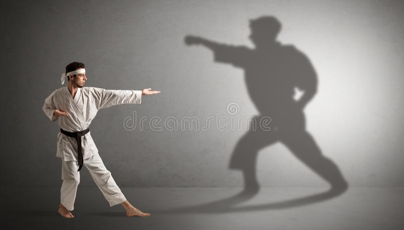 Karate man confronting with his own shadow. Young karate man confronting with his own shadown royalty free stock photo