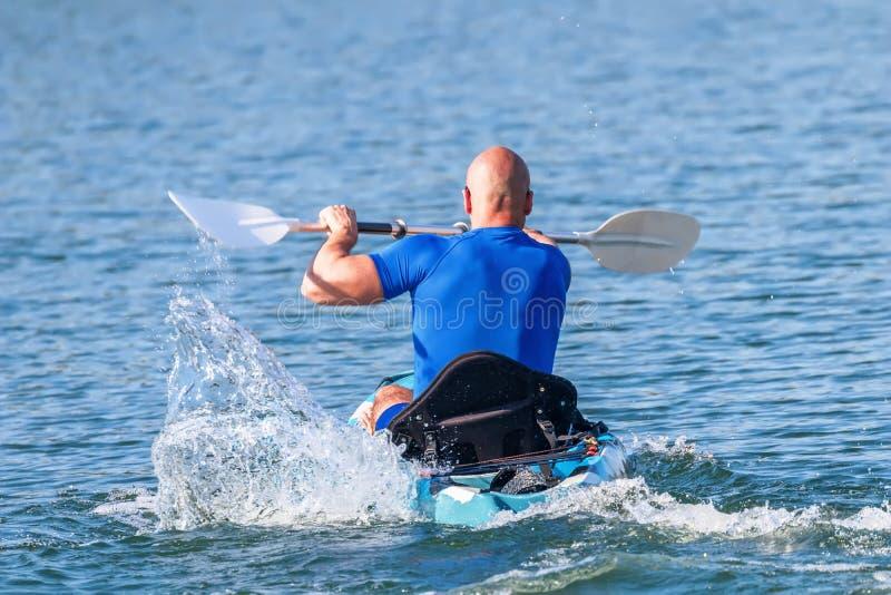 Young Kayaker Paddling Kayak. Sportsman kayaking Blue Water stock photos