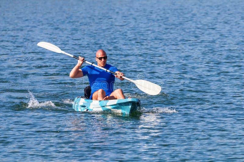 Young Kayaker Paddling Kayak. Sportsman kayaking Blue Water royalty free stock image