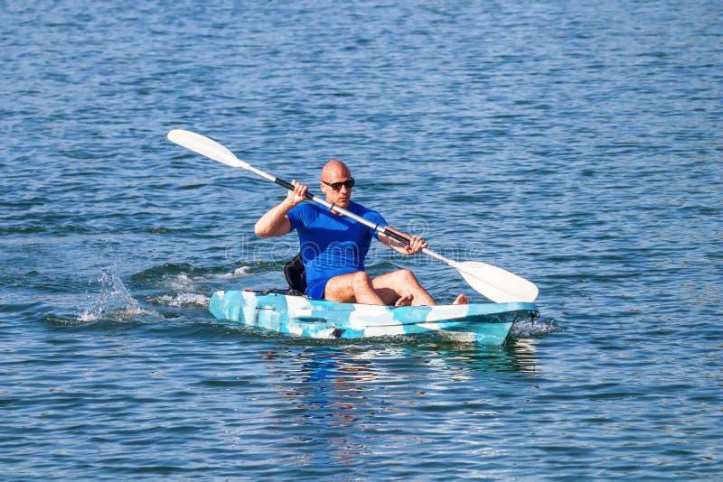 Young Kayaker Paddling Kayak. Sportsman kayaking Blue Water stock photography