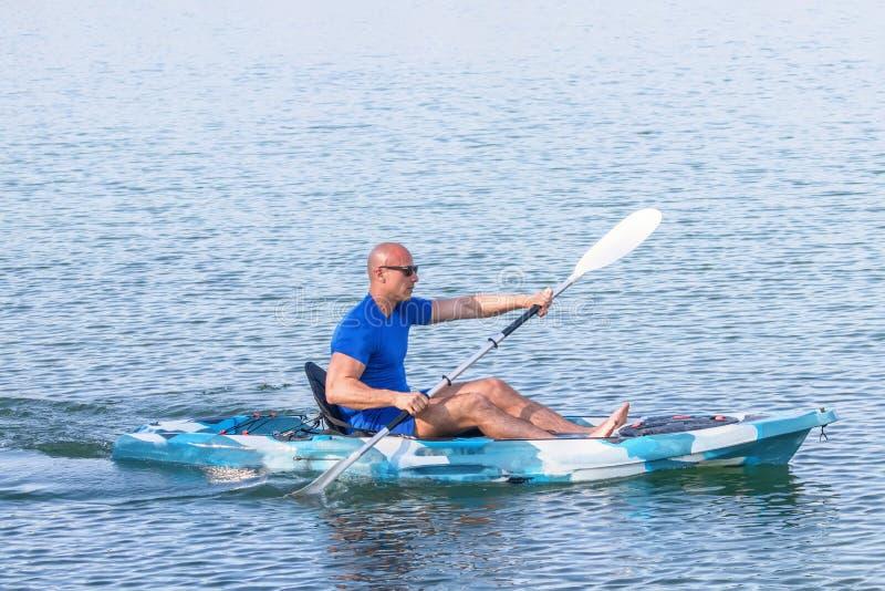 Young Kayaker Paddling Kayak. Sportsman kayaking Blue Water stock photo