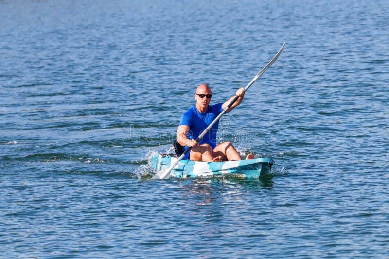 Young Kayaker Paddling Kayak. Sportsman kayaking Blue Water stock images