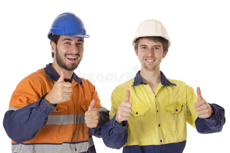 Young and Keen Workers. Two young men dressed in their work clobber, giving a thumbs up stock photography