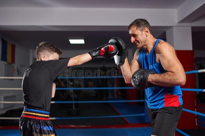 Kickboxer kid and his coach. Young kickbox fighter hitting mitts with his coach stock photos