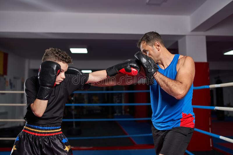 Kickboxer kid and his coach. Young kickbox fighter hitting mitts with his coach stock photo