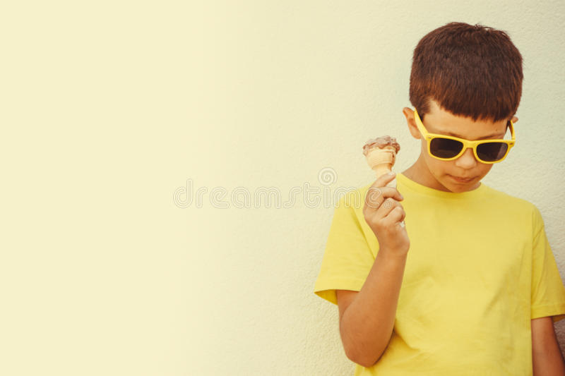 Young kid boy child eating ice cream. stock photos
