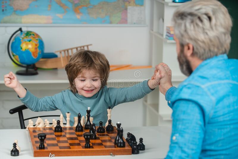 Young kid boy playing chess with father and having fun. Educational games. Handsome father and son are playing chess stock photos