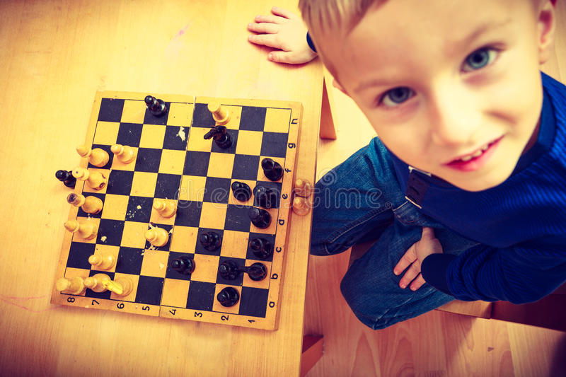 Young kid boy playing chess having fun. Intelligent, smart kids, games good for brain intelligence concept. Young kid boy playing chess and having fun royalty free stock photos