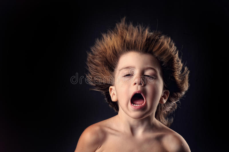 Young kid with crazy expression and flying hair stock image