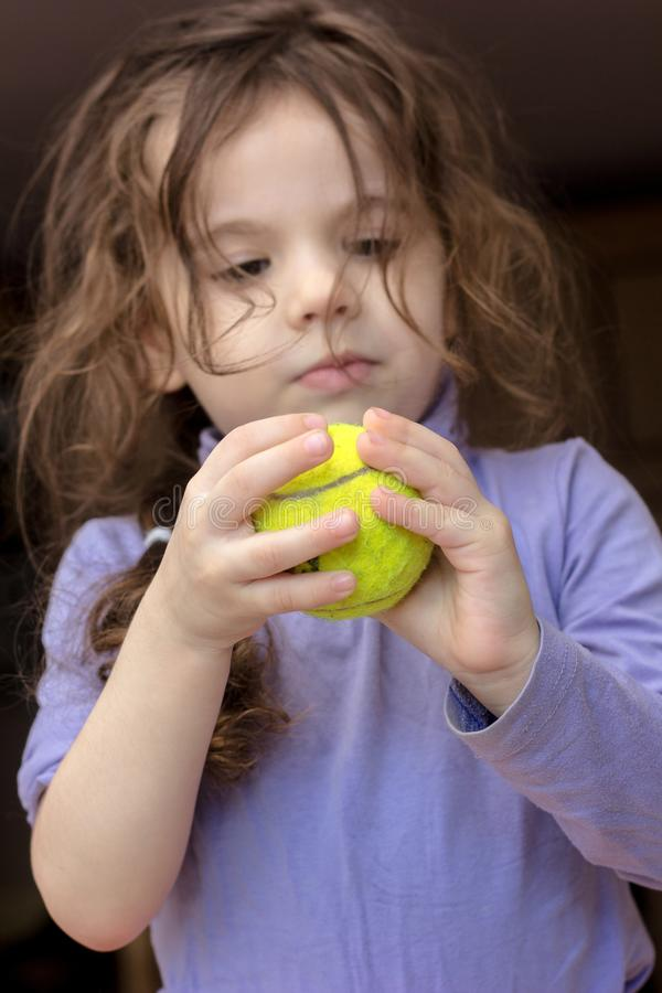 Young kid girl holding tennis ball in hands. Young kid girl holding tennis ball in hands stock image