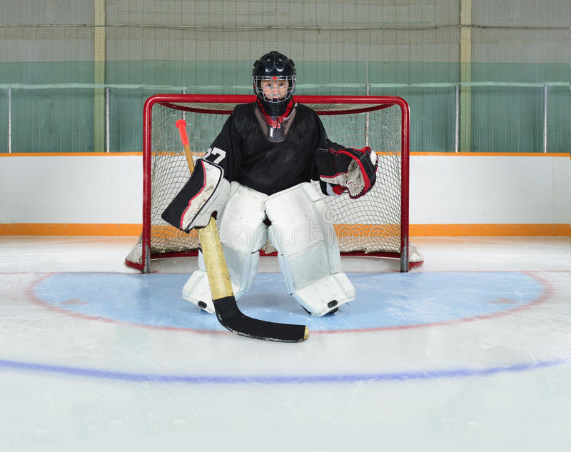 Young Kid Goalie In Hockey Net Crease. A Young Hockey Goalie Kid Protects his Net from a Goal stock images