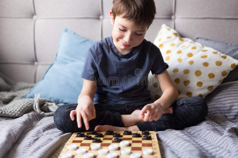 Young kid hands playing checkers table game on bed. Stay at home Quarantine concept. Board game and kids leisure concept. Family time royalty free stock images