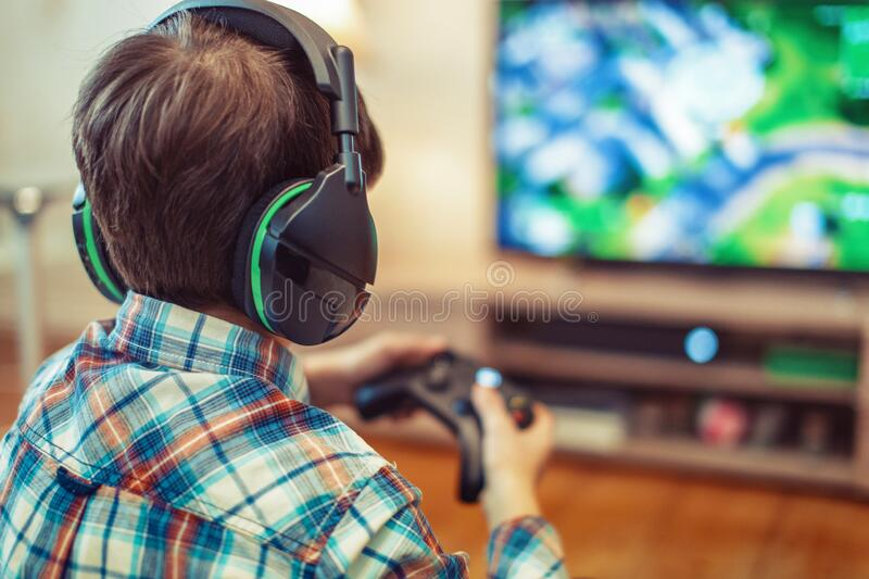 Young kid playing mass multiplayer game online royalty free stock photography