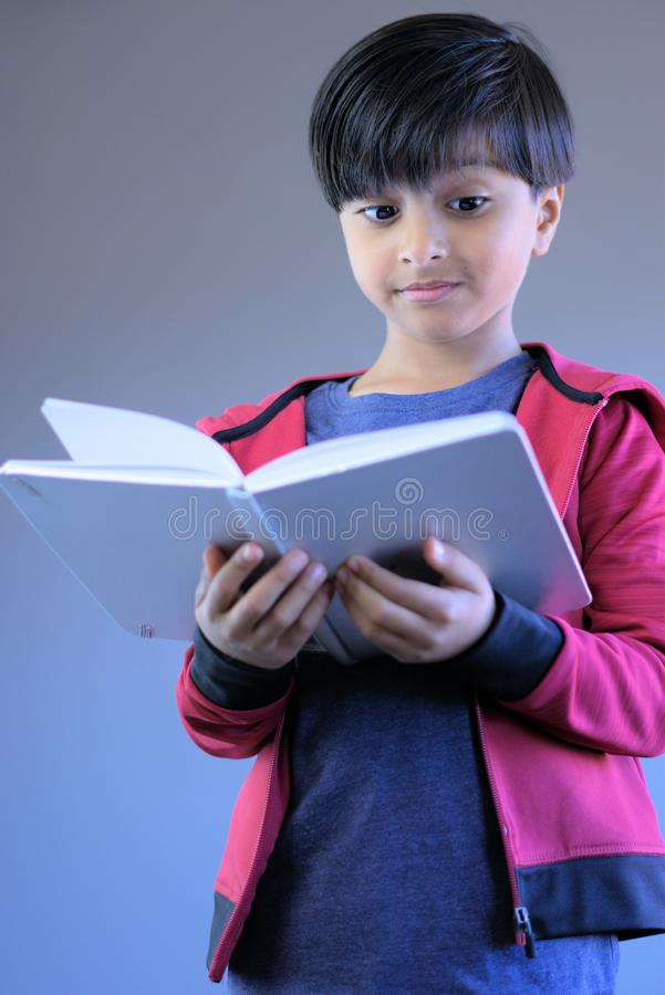 Curious child reading book looking with surprised expression royalty free stock photos