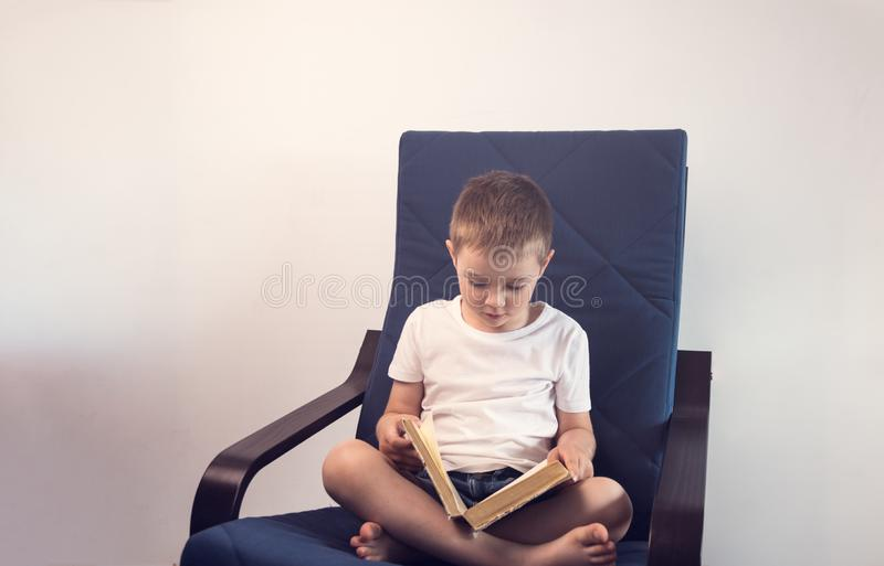 Young kid reading an interesting book sitting on the blue armchair. Concept of reading an interesting and exciting book everywhere stock photography