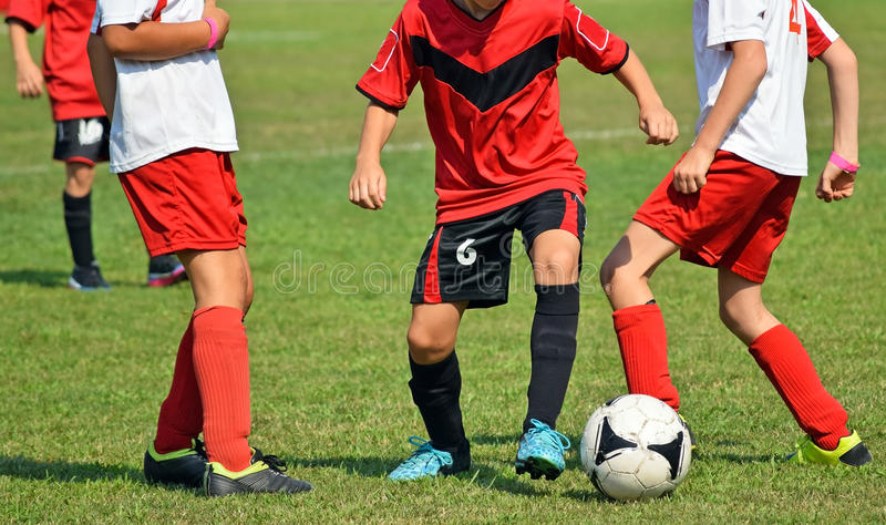 Young kids in action at the soccer match. Outdoors royalty free stock images