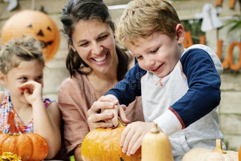 Young kids carving Halloween jack-o`-lanterns stock photo