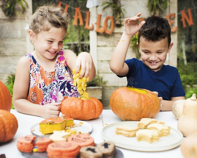 Young kids carving Halloween Jack-o-lanterns royalty free stock photo