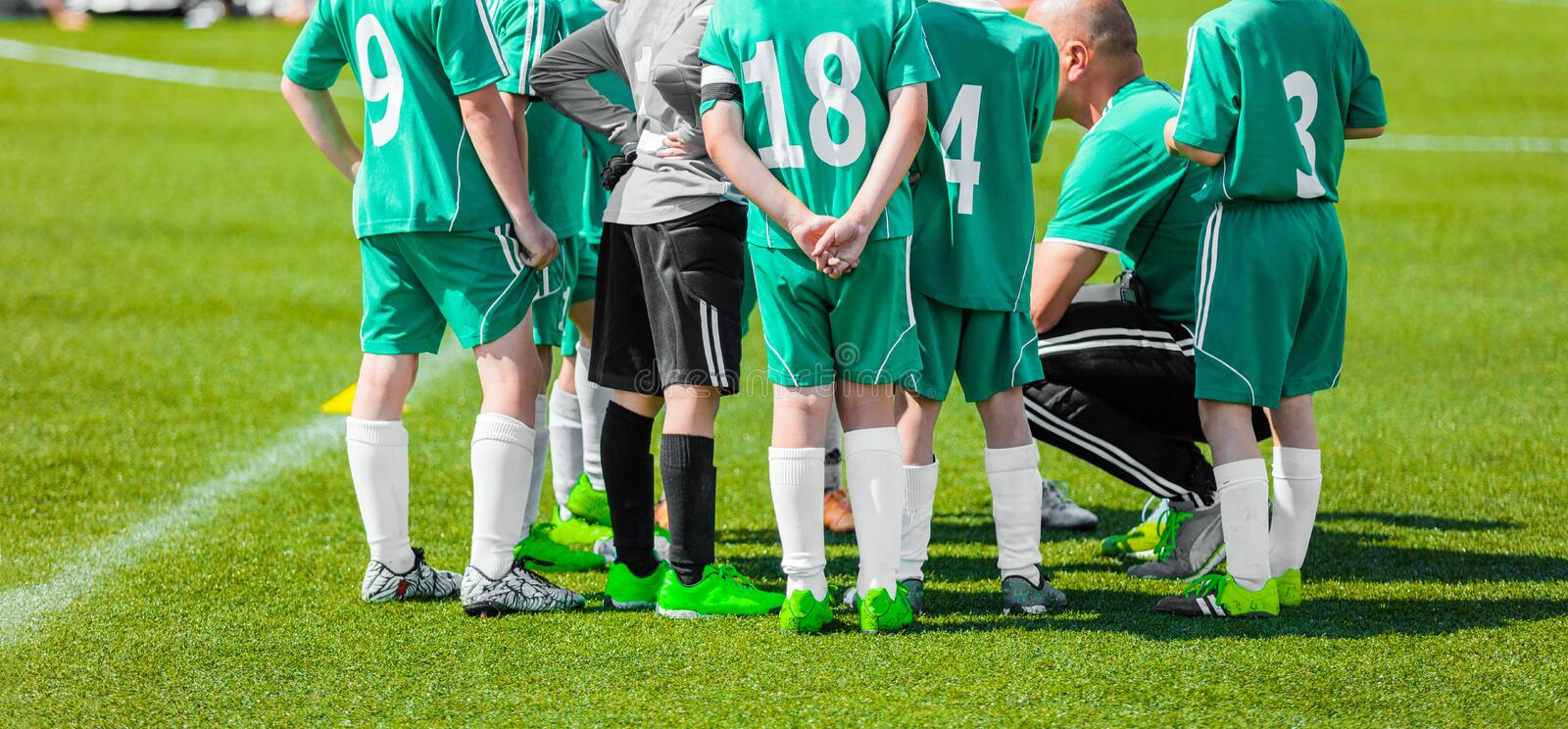 Young Kids with Chaoch on a Soccer Team. Soccer coach giving young football team instructions. Youth soccer team before final game. Football; soccer match for stock photography