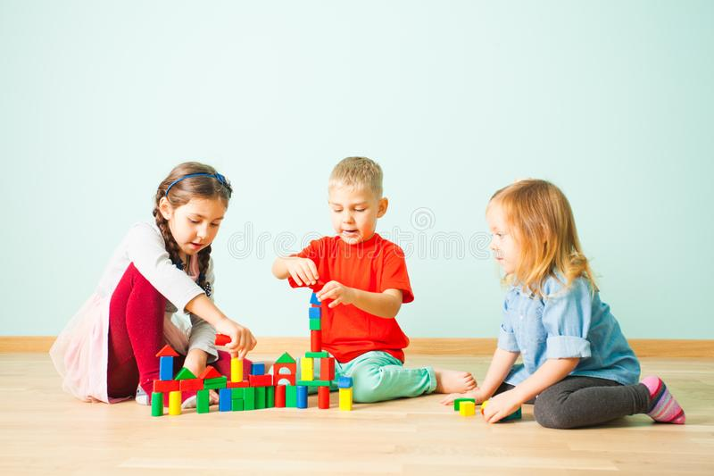 Young kids constructing towers from wooden blocks stock image