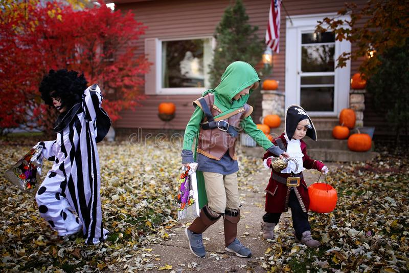 Young Kids Dressed in Costumes Trick or Treating on Halloween in America stock photography