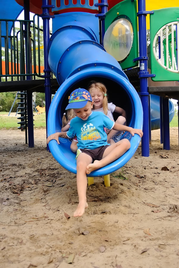 Young kids exiting a tube slide royalty free stock photos