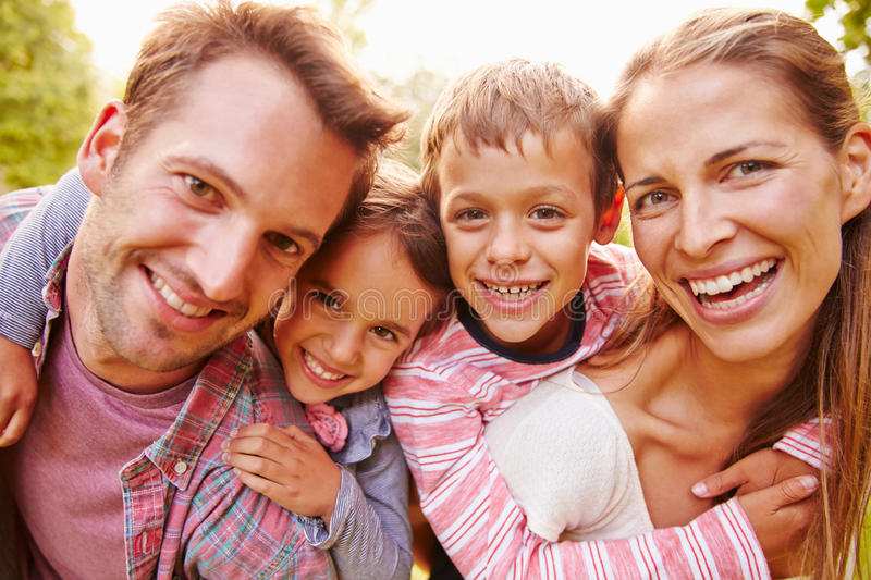 Young kids hugging parents outdoors, close up portrait stock image
