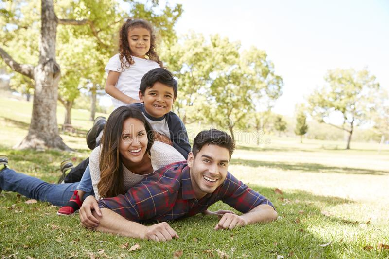 Young kids and parents lying in pile on the grass, portrait royalty free stock images