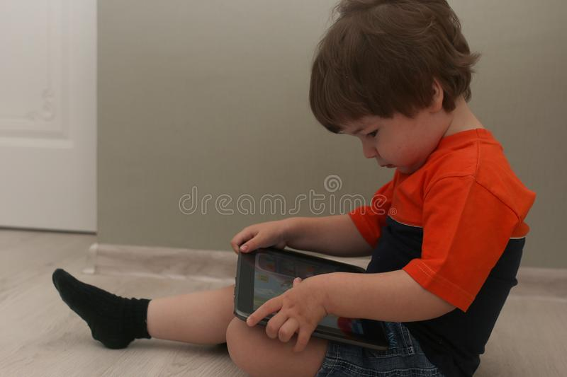 Young kid playing on a floor in a room. Young kids playing on a floor in a room royalty free stock images