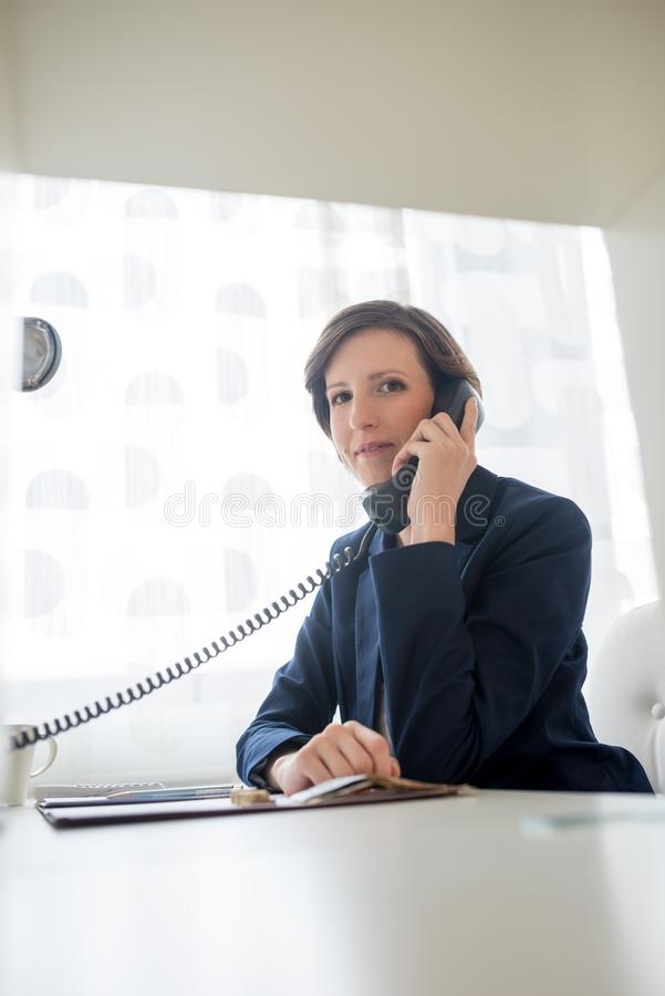 Business woman talking on landline telephone. Young kind business woman sitting at her desk talking on a black landline telephone stock photos